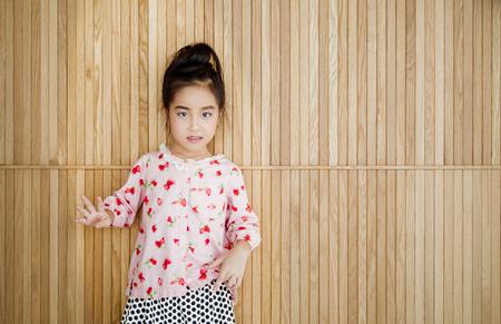 Portrait of happy little girl , wood background