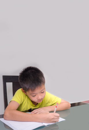 Asia little student boy studying and doing his homework  at home,  on the table, home education