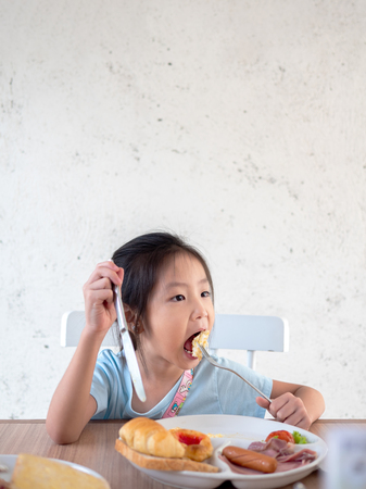 Asian girl child eating american breakfast in the cafe