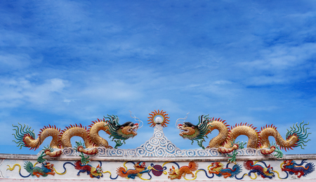 Chinese dragon and deva statue on the chinese temple roof with blue sky background Stock Photo