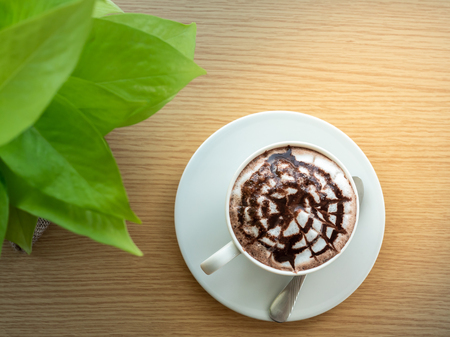 hot chocolate in a white cup , on wood table, near windows Imagens