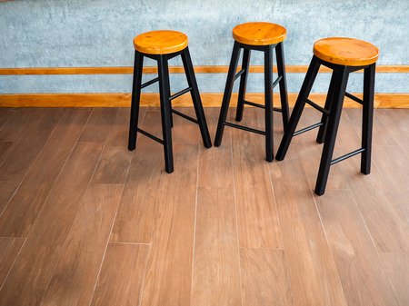 Simple wooden bar stools , 3 chair in group at indoor coffee bar.