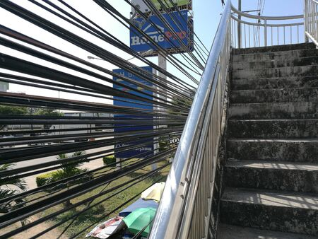 Thailand, Chonburi : The footbridge over the highway road in front of Home Pro store, have many cables of telephone , fiber, Electronic and cable line, December 18, 2018 in Chonburi.