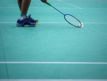Indoor badminton court with the player leg , shuttle cock and the racquet, selective focus Imagens