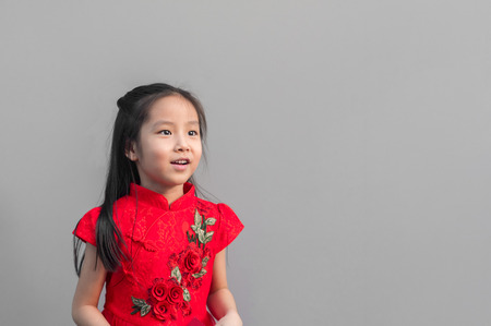 Cute Asian girl in chinese cheongsam and Tradition Chinese dress with red envelope , Chinese new year concept , grey background