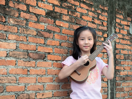 Little asian child play the ukulele, old brick wall background Imagens