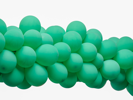 Green color decorated balloons in a row over white background , with clipping path