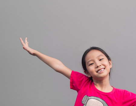 Asian little cute girl smile with her broken tooth , grey background Imagens