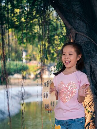 Little asian child girl play the tambourine, in the garden under the big tree