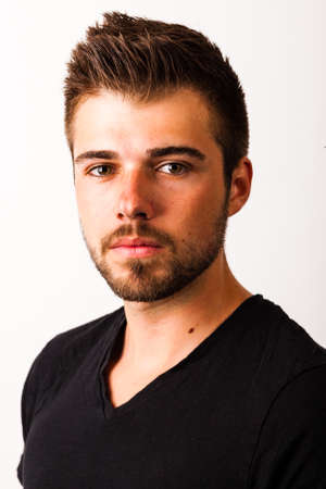 Portrait of a young man with 3-days beard in front of white background