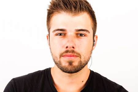 ear phones: Portrait of a young man with 3-days beard in front of white background