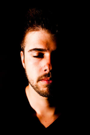 Portrait of a young man with 3-days beard in front of black background