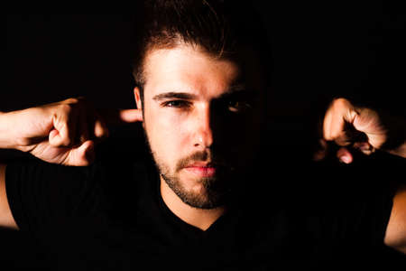 Portrait of a young man with three - day beard puts his fingers in his own ears.