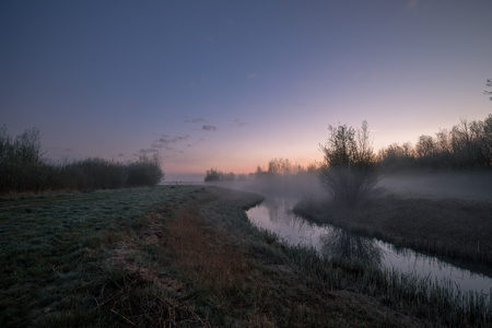 Morning Fog With Beautiful Colorful Sunrise At Grassland And Small Stream