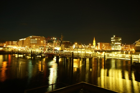 Kiel illuminated skyline at night with harbour and glowing sky