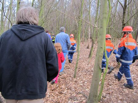 A group of people incl volunteer fire brigade in the forest photo