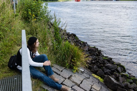 19 years old: A young woman sitting by the water of the Kiel Canal and dreams
