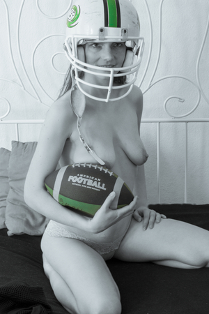 a woman is posing naked and nude as an American Football player