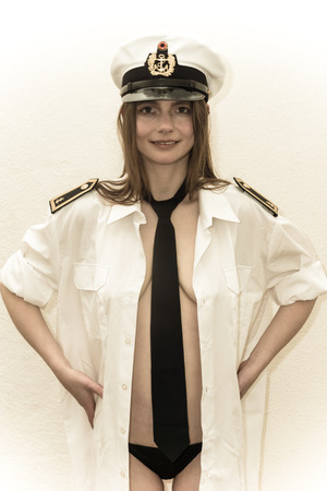 a woman is posing naked and nude as an officer of the German Navy Stockfoto