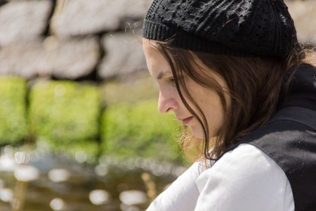 A young woman sitting by the water of the Kiel Canal and dreams