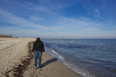 A young woman is walking around at the beach of Kappeln photo