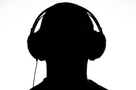 Male form wearing headphones in silhouette Stock Photo