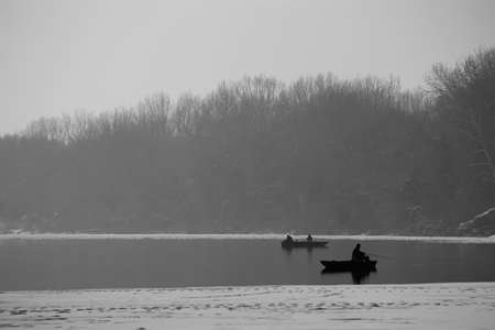 Fishing at a cold and misty lake photo