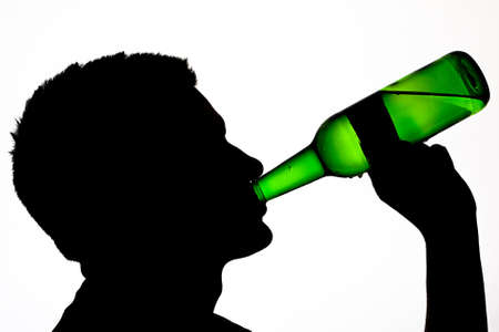 Male silhouette drinking beer lit from behind