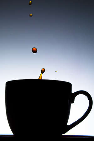 Coffee splashing into cup in silhouette photo