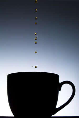 Coffee dripping into cup in silhouette photo