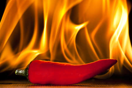 spicy chilli: A chilli pepper against a flaming background Stock Photo