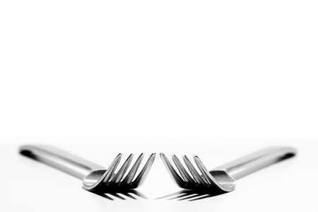 Two forks against a white background