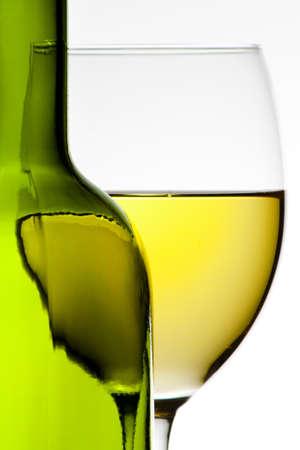 white wine bottle: Botella de vino y vino blanco en un vaso de vino