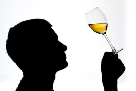 wine testing: Silhouetted male examining white wine Stock Photo