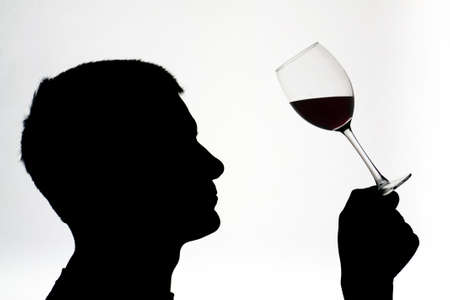 Silhouetted male examining red wine