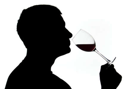 tasting: Silhouetted male examining red wine