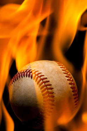 Old weathered baseball enulfed in flames