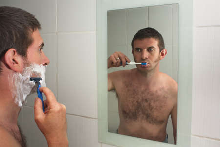 Male figure multi tasking, shaving and brushing teeth in reflection in mirror photo