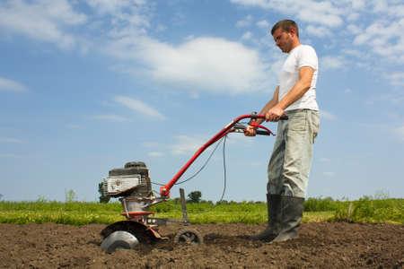 Man using cultivator in a rural scene