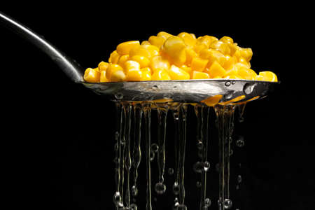 Sweet corn being drained through a slotted spoon