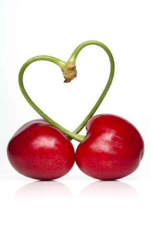 Pair of cherries against a white backdrop with the stems forming a heart symbol Stock Photo