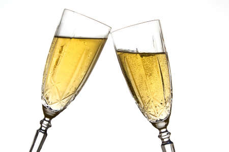 Clinking champagne glasses against a white background