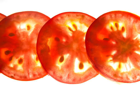 Thinly sliced fresh tomato backlit against a white background photo