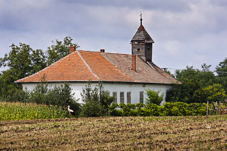 Old abandoned Hungarian church next to a ploughed field with a stork