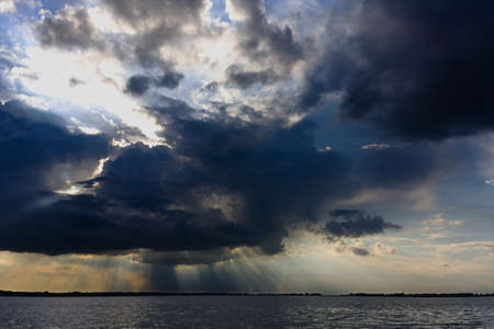 crepuscular: Crepuscular rays from a dark cloud over Lake Tisza in eastern Hungary Stock Photo