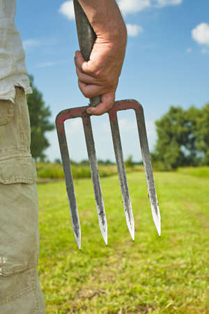 Gardener off to work with a pitch fork or garden fork on a summers day