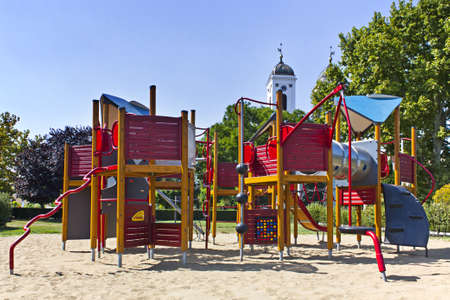 Deserted childrens playground on a beautifuly warm summers day over looked by church tower Stock Photo - 10378184