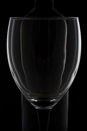 Impression of a wine glass and wine bottle against a black background photo