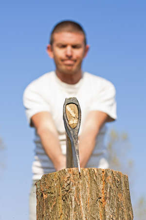 splitting up: Close up of axe hed splitting a log with a male figure with narrow depth of focus against a beautiful blue sky