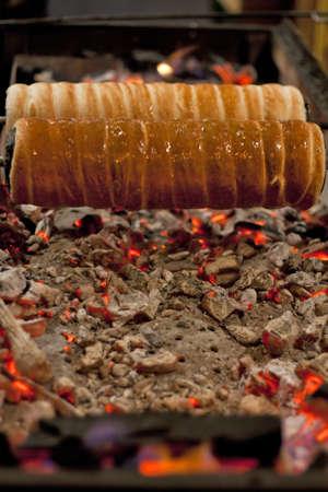 embers: Kurtoskalacs or traditional hungarian Chimney Cake cooking over burning embers